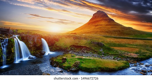 Kirkjufell waterfall and mountain with colorful dramatic sky during sunset, iceland. Amazing nature landscape. Iconic location for landscape photographers. greative artistic image. postcard
