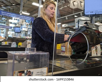 Kirkland, WA / USA - circa April 2020: Cashier behind a plexiglass wall at a checkout counter inside a QFC grocery store during the coronavirus outbreak.