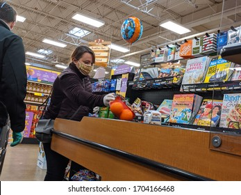 Kirkland, WA / USA - circa April 2020: Customers with face masks and protective gloves loading groceries onto the checkout conveyor belt at a Fred Meyer grocery during the COVID-19 pandemic.