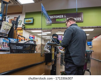 Kirkland, WA / USA - circa April 2020: Cashier behind a plexiglass wall at a checkout counter inside a Fred Meyer grocery store during the coronavirus outbreak