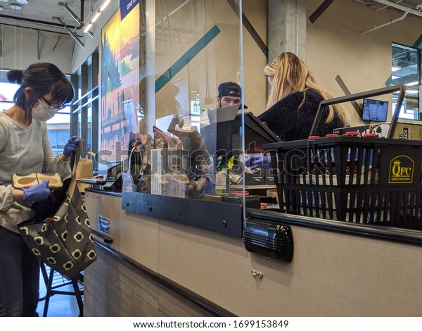 Kirkland, WA / USA - circa April 2020: Cashier behind a plexiglass wall at a checkout counter inside a QFC grocery store during the coronavirus outbreak
