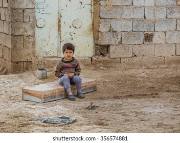 Kirkuk, Iraq - December 29, 2015: orphan small boy left in Iraqi countryside ,his parents were killed by ISIS terrorists ,and now old woman taking care of him in Iraqi desert