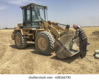 Kirkuk, Iraq - May 10, 2017: worker putting cement inside the bucket of backhoe