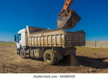 Kirkuk, Iraq - November 24, 2015: Excavator bucket fills huge dump truck in Iraqi desert