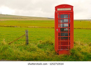 Kirkwall, Orkney Islands / United Kingdom - August 2014: Lonely red phone booth in a rural scenery.