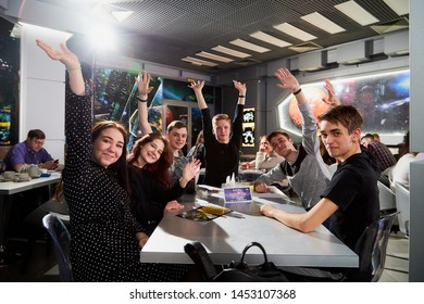 Kirov, Russia - April 18, 2019: People at tables in cafe or restaurant posing for photographer during Intellectual game in which the team give the answers to different questions