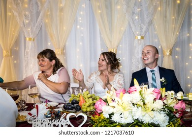 Kirov, Russia - July 27, 2018: Wedding banquet. The bride and groom at the table. Everyone is having fun. Smile and kiss. Wedding feast