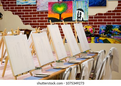 KIROV, RUSSIA - JUNE 23, 2017: Canvases standing in a row on the long table in the local art studio in preparation for the artistic masterclass