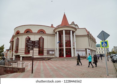 Kirov, Russia - October 06, 2018: Vintage beautiful building in grey and red colours and turrets on the roof with cloudy sky background. Puppet theatre in Kirov