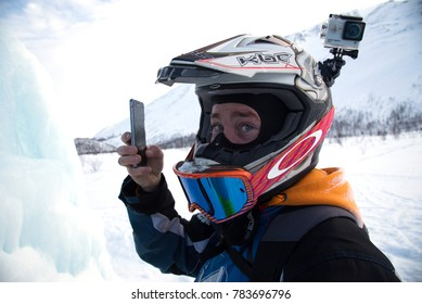 Kirovsk, Russia - 04/08/2017: snowmobile rider in helmet with camera go-pro makes selfie photo . Mountain pass in  Khibiny Mountains,  Kola Peninsula.