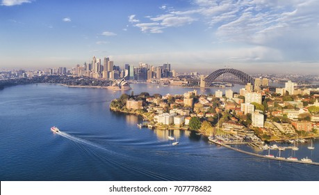 Kirribilli yacht club, headland and marina in front of Sydney city CBD, harbour bridge and landmarks around waters of Sydney Harbour under warm morning sun light.