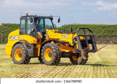 Kirwee, Canterbury, New Zealand, March 27 2019: A farmer demonstrates how the JCB telehandler works so well stacking haybales at the South Island Agricultural Field Days