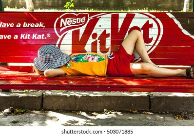 Kishinev, Moldova- August, 14: Child sleeping on the bench with the inscription Nestle Kit-Kat
