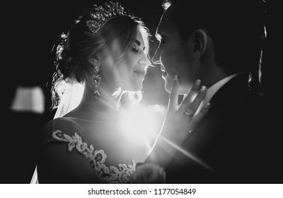 The kiss of the bride and groom in the back light. Backlight. Shining silhouette. Wedding jewelry. Black and white photography.