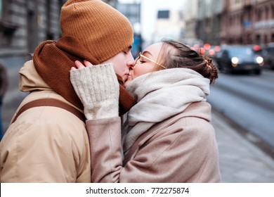 A kiss closeup portrait of beautiful couple in love posing outdoor in cold winter.