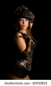 Kiss from pretty girl in a bronze corset coquets holds a hand in a lacy glove on a the cylinder hat