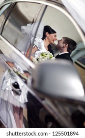 kiss in the reflection of a car
