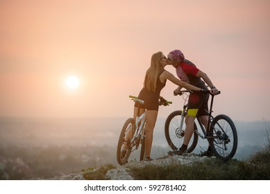 Kiss of romantic young couple on bicycles against sunset. Bikers on the top of a hill. Blurring background. Copy space