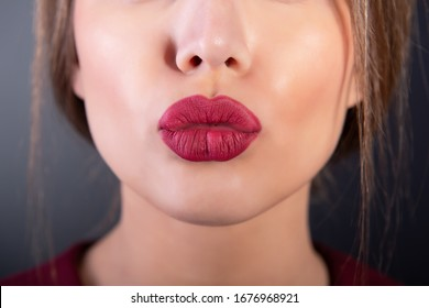 Kiss sexy lips of young woman over gray background. Love, feeling, positive expressions