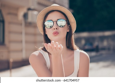 Kiss for you! Happy carefree girl on a holiday is sending an air kiss to her lover. She is in a fashionable hat and sunglasses