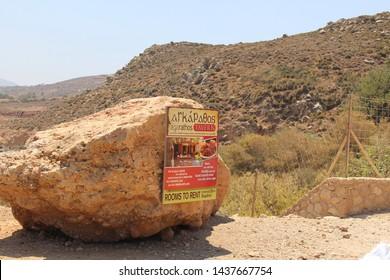 KISSAMOS, CRETE ISLAND, GREECE - JULY 29, 2016: Agarathos Tavern billboard attached on a big rock on the way to the famous Balos beach.