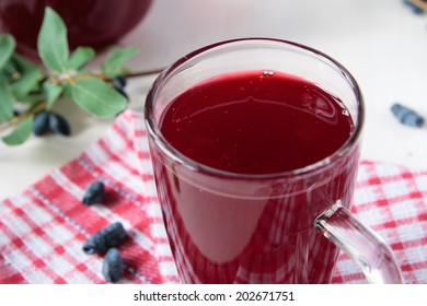 Kissel of honeysuckle berries in a glass and a jug