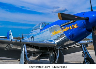 Kissimmee, Florida / USA - March 5, 2016: Closeup of Slender, Tender & TALL, a P-51D warbird, parked on the tarmac at Stallion 51, in Kissimmee, Florida. Blue sky and clouds form the backdrop.