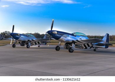 Kissimmee, Florida/USA - March 5, 2016: P-51 Mustang warbirds Crazy Horse, and Crazy Horse 2, parked side by side on tarmac at Stallion 51, in Kissimmee, Florida, backlit by a brilliant blue sky.