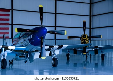 Kissimmee, Florida/USA - March 5, 2016: P-51 Mustang warbirds Crazy Horse 2, and The Little Witch, parked in a hangar at Stallion 51, in Kissimmee, Florida. Partial American flag in the background.