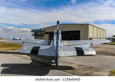 Kissimmee, Florida/USA - March 5, 2016: View from behind, straight from the tail to nose of P-51 Mustang warbird Slender, Tender & TALL, at Stallion 51 in Kissimmee, Florida. Hangar in background.