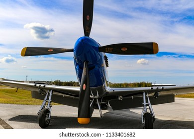 Kissimmee, Florida/USA - March 5, 2016: Front view of Slender, Tender & TALL, a P-51D warbird, parked on the tarmac at Stallion 51, Kissimmee, Florida. Blue sky and clouds in the background.