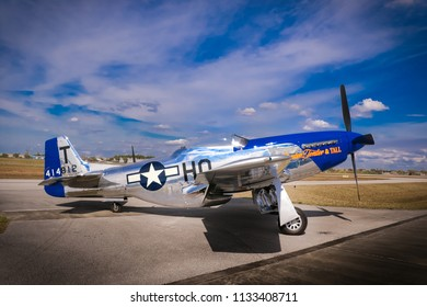 Kissimmee, Florida/USA - March 5, 2016: Side view of Slender, Tender & TALL, a P-51D warbird, parked on the tarmac at Stallion 51, Kissimmee, Florida.  Blue sky and clouds behind. Sunlight reflection.