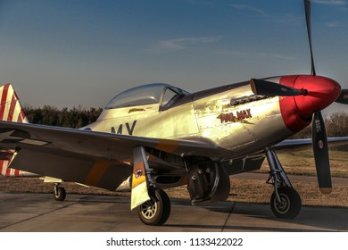 Kissimmee, Florida/USA - March 5, 2016: Closeup of Mad Max, a P-51D Mustang warbird, parked on the tarmac at Stallion 51, Kissimmee, Florida. Sunset reflecting off of fuselage. Blue sky above.