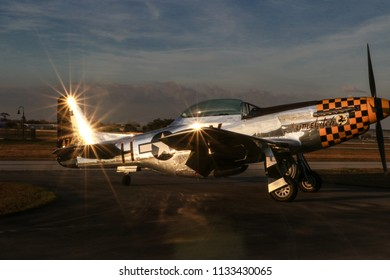 Kissimmee, Florida/USA - March 5, 2016: The Little Witch, a P-51D warbird, parked on the tarmac at Stallion 51, Kissimmee, Florida. Sunset reflections on tail and body creating dramatic sun flares.