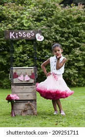 Kissing booth.  Adorable little girl standing next to a kissing booth.