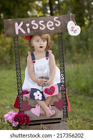 The Kissing Booth.  Adorable little girl sitting at a kissing booth.