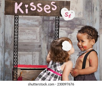 The Kissing booth.  Two adorable toddlers at a kissing booth.