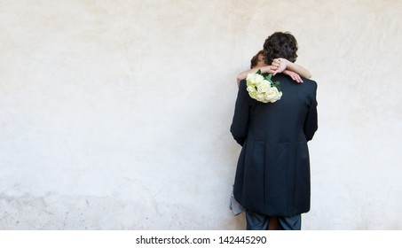 Kissing bride and groom embracing against a wall