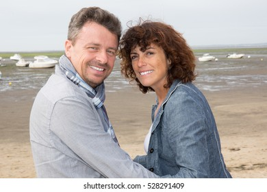 kissing couple forties in front of ocean beach side