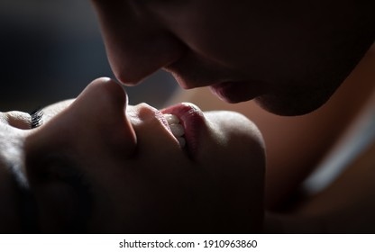 Kissing couple at night. Sex in dark hotel room. Lips of woman and man. Embrace on a date or romantic movie scene. Erotic sexual fantasy. Tender love in relationship. Passionate foreplay and intimacy.