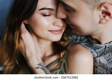 Kissing couple portrait. Happy couple deeply in love sharing a romantic kiss, closeup profile view of their faces