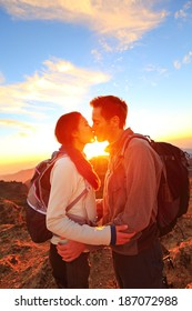 Kissing couple - romantic lovers hiking at sunset sharing kiss enjoying sunshine and love on beautiful hike in mountain nature landscape. Young interracial couple, Asian woman, Caucasian man in love.