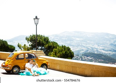Kissing couple sits before yellow retro Fiat 500 with great view behind them