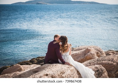Kissing couple sitting on rock from the back over beautiful seascape landscape