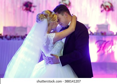 Kissing and embracing newlyweds dancing in the restaurant hall