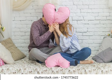 kissing guy and girl who are closing with a pink heart, sitting on the bed against a white brick wall