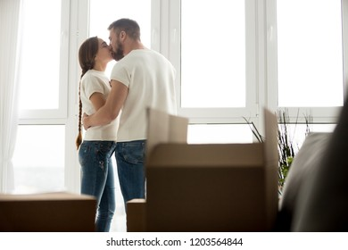 Kissing loving young couple in new apartment with unpacked belongings in cardboard boxes, family just arrived in new house, thinking about good future in own rental house, beginning live together