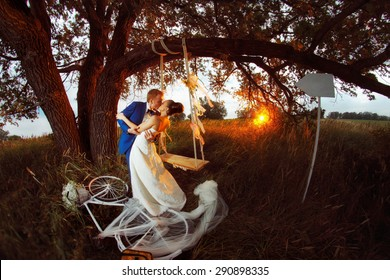 Kissing wedding couple near bicycle at summer sunset background