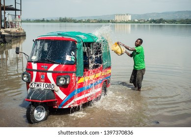 Kisumu / Kenya - September 28, 2013: a man washes his tuc tuc in the waters of Lake Victoria