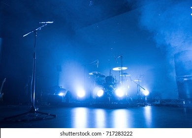 A kit of drums and a microphone on an empty stage in blue smoke before the concert